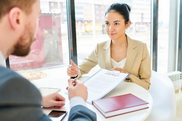 Donna di affari che mostra contratto al cliente