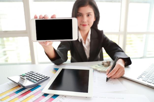 Donna di affari che mostra il telefono cellulare dello schermo in bianco con la compressa sulla tavola