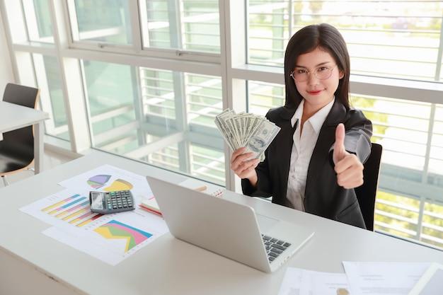 Donna di affari che mostra rapporto e grafico di sintesi dell'azienda con soldi sulle mani
