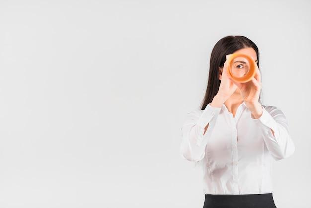 Donna di affari che osserva attraverso il rotolo di carta