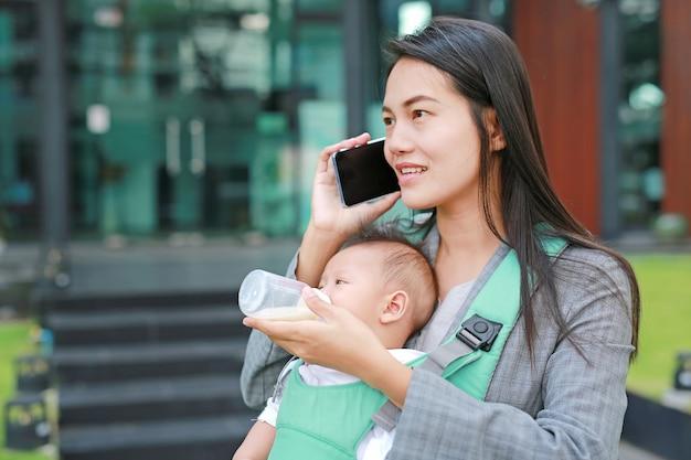 Donna di affari che parla dal telefono con portare neonato infantile