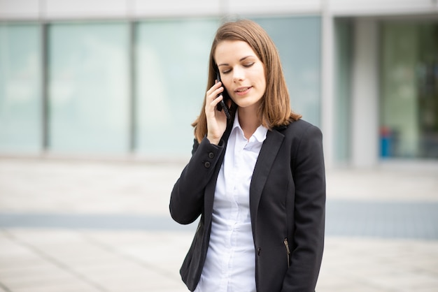 Donna di affari che parla sul suo telefono cellulare mobile