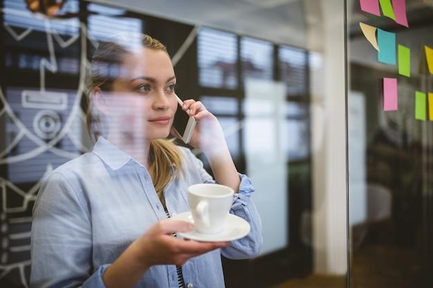 Donna di affari che parla sul telefono durante la pausa caffè