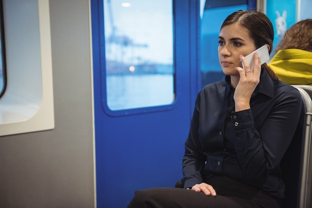 Donna di affari che parla sul telefono mentre sedendosi in treno