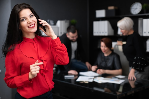 Donna di affari che parla sul telefono sopra degli impiegati che discutono progetto