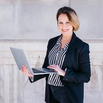 Donna di affari che passa in rassegna il computer portatile sulla via