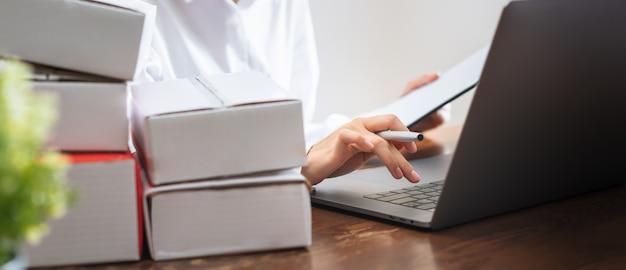 Donna di affari che per mezzo del computer portatile che controlla ordine per il cliente e la consegna online.