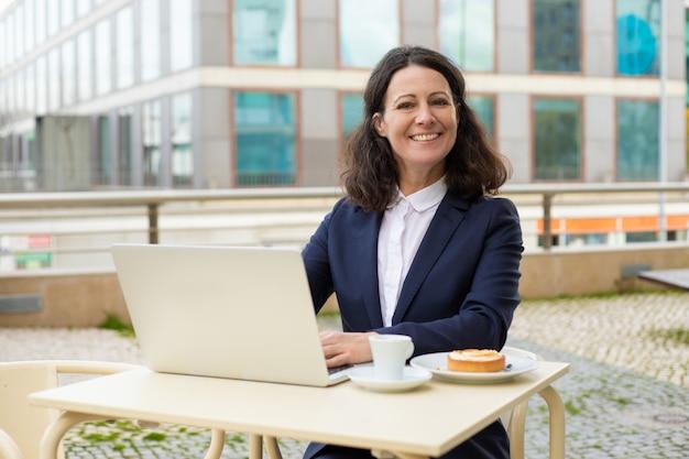 Donna di affari che per mezzo del computer portatile e sorridere