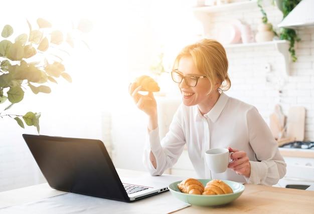 Donna di affari che per mezzo del computer portatile mentre mangiando croissant