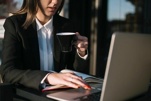 Donna di affari che per mezzo del computer portatile mentre mangiando tazza di caffè