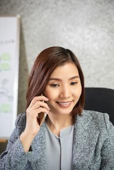 Donna di affari che per mezzo del telefono cellulare all'ufficio
