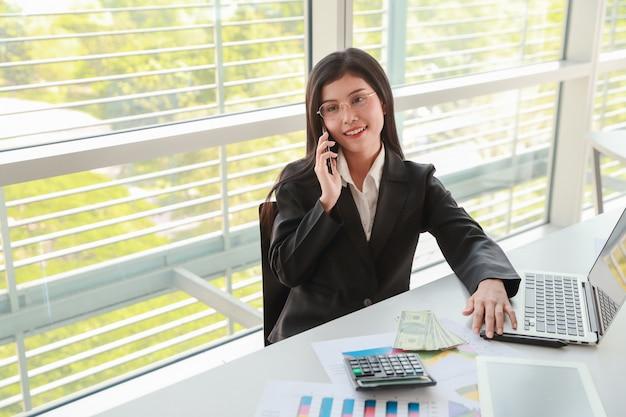 Donna di affari che per mezzo del telefono cellulare e del computer mentre lavorando al rapporto di sintesi della società con il grafico
