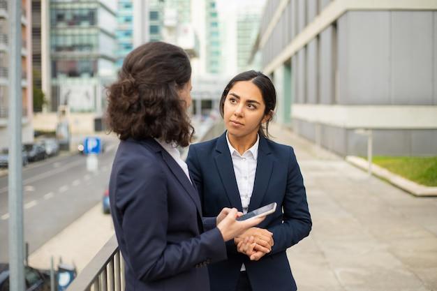 Donna di affari che per mezzo dello smartphone e esaminando i colleghi