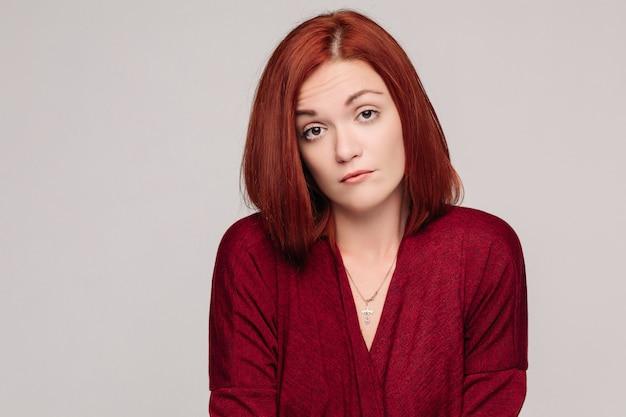 Donna di affari che porta camicia rossa che ha emozione passiva e che sembra frustrata.