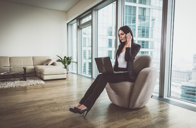 Donna di affari che posa nel suo appartamento
