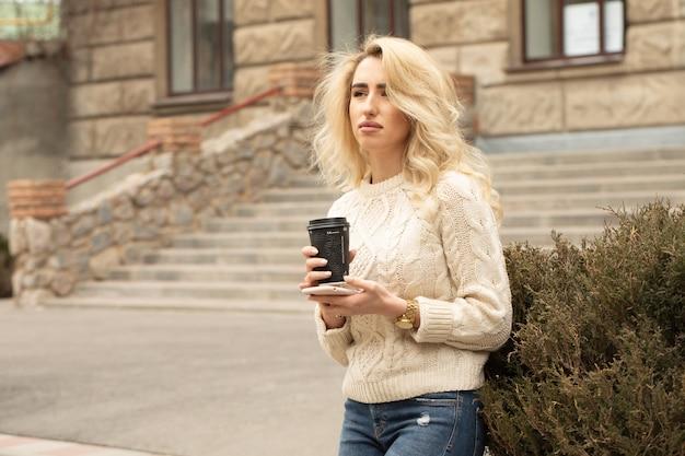 Donna di affari che prende una pausa caffè e che per mezzo dello smartphone