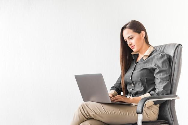 Donna di affari che resta sul suo computer portatile con lo spazio della copia