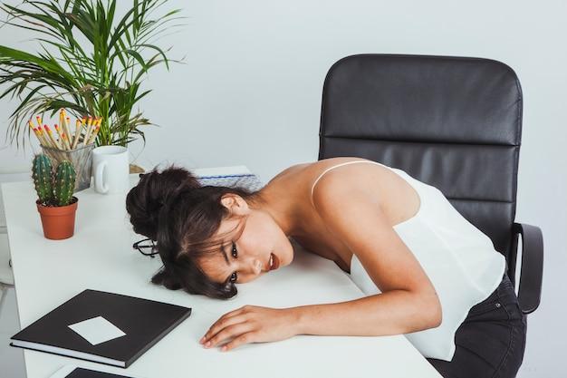 Donna di affari che riposa sulla sua scrivania