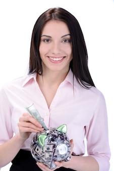 Donna di affari che risparmia soldi in un porcellino salvadanaio.