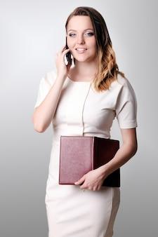 Donna di affari che rivolge allo smartphone all'ufficio