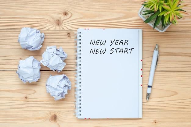 Donna di affari che scrive nuovo anno nuovo inizio con il taccuino