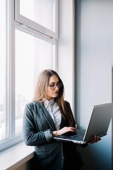 Donna di affari che scrive sulla tastiera del computer portatile
