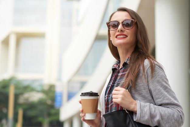 Donna di affari che si dirige fuori per lavorare con caffè asportabile di mattina