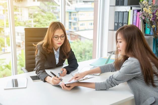Donna di affari che si incontra e che consulta insieme nell'ufficio.