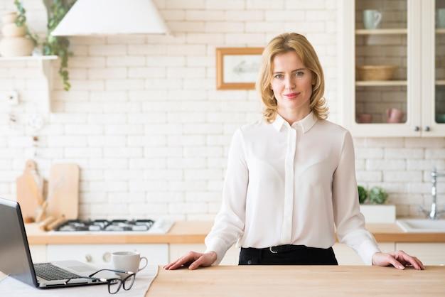 Donna di affari che si leva in piedi alla tabella con il computer portatile