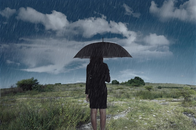 Donna di affari che si leva in piedi con un ombrello in pioggia