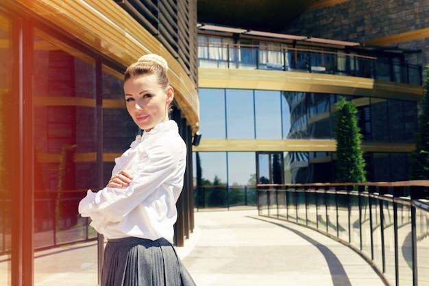 Donna di affari che si leva in piedi vicino al suo ufficio di mattina