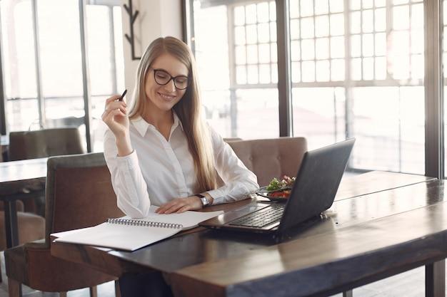 Donna di affari che si siede al tavolo con un computer portatile