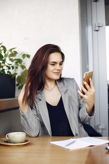 Donna di affari che si siede al tavolo in un caffè e di lavoro