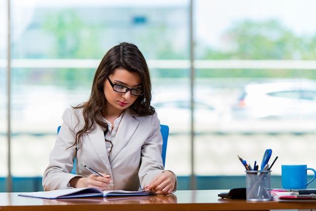 Donna di affari che si siede alla scrivania