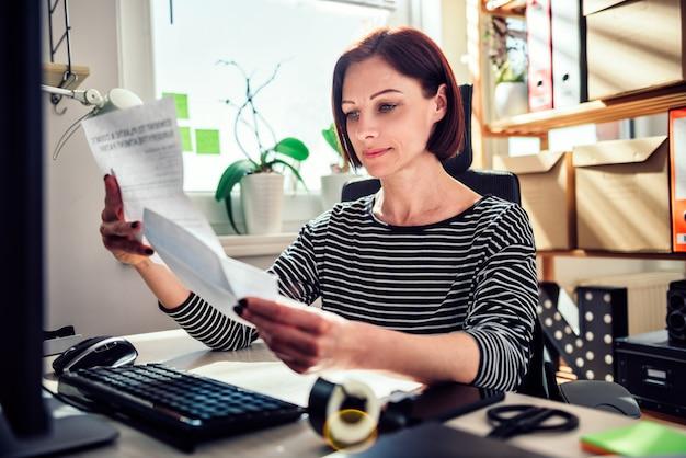 Donna di affari che si siede allo scrittorio e che legge posta all'ufficio