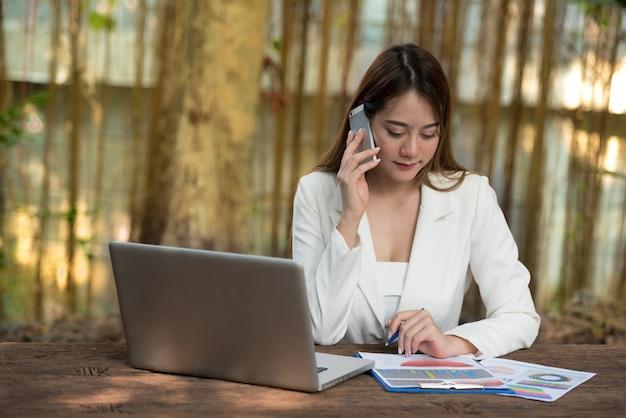Donna di affari che si siede allo scrittorio e che parla sullo smartphone con il computer portatile e sul grafico sulla tavola
