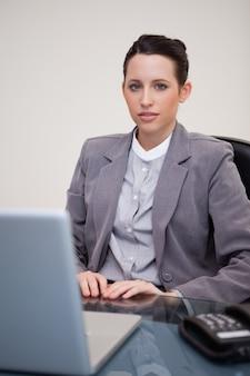 Donna di affari che si siede dietro lo scrittorio