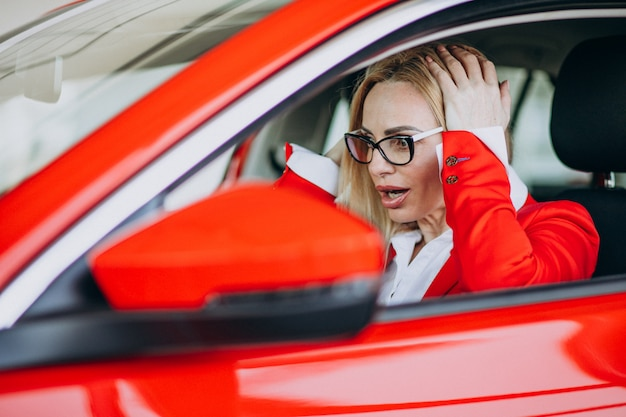 Donna di affari che si siede in una nuova automobile in una sala d'esposizione dell'automobile