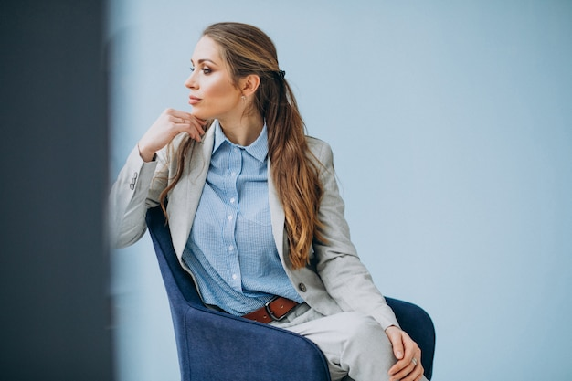 Donna di affari che si siede nella sedia ad un ufficio