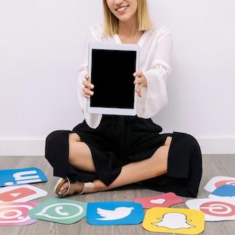Donna di affari che si siede sul pavimento con le icone di media sociali che mostrano compressa digitale