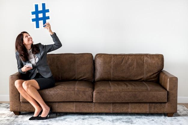 Donna di affari che si siede sull'icona della tenuta del divano
