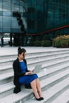 Donna di affari che si siede sulla scala che lavora al computer portatile