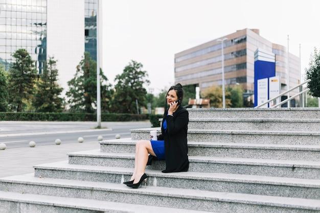 Donna di affari che si siede sulla scala che parla sullo smartphone all'aperto
