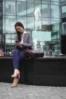Donna di affari che si siede vicino alla fontana e che per mezzo del telefono cellulare