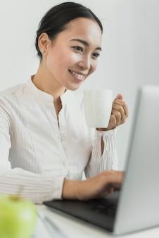 Donna di affari che sorride al computer portatile