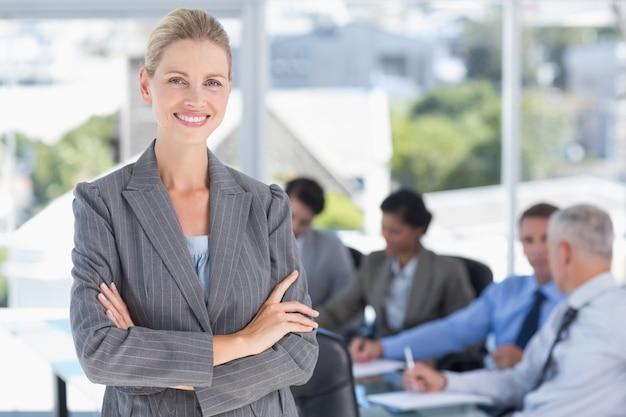Donna di affari che sorride alla macchina fotografica con i colleghi dietro