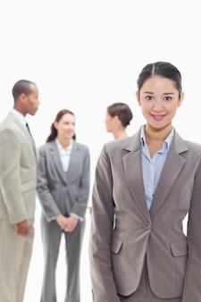 Donna di affari che sorride con i colleghe nei precedenti