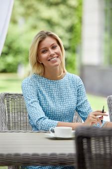 Donna di affari che sorride con il caffè ad una tavola sul terrazzo di estate. copyspace, verde.