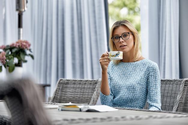 Donna di affari che sorride con il caffè ad una tavola sul terrazzo di estate.