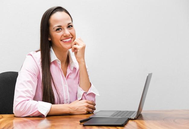 Donna di affari che sorride con la priorità bassa bianca